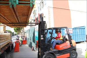 FROM HERE TO THERE: A forklift operator raises a load of lumber at the site of Parking Structure No. 6 on Monday. (Photo by Daniel Archuleta)