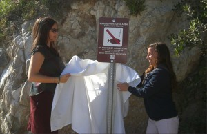 Liz Crosson and Amanda Gruen of L.A. Waterkeeper unveil a new sign in Malibu warning people not to fish in newly created Marine Protected Areas. (Photo by Melonie Magruder)