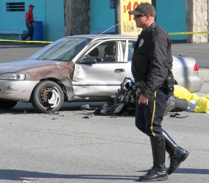 A Santa Monica police officer inspects the scene of a fatal traffic accident at the corner of 25th Street and Pico Boulevard on Monday. (Daniel Archuleta daniela@smdp.com)