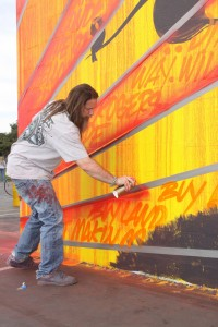 Graffiti artist Kelly 'Risk' Graval works on a mural at Will Rogers Elementary School last week. (Ray Solano editor@smdp.com)