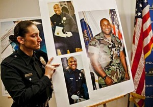 An LAPD officer holds up photos of suspected cop killer  Christopher Dorner. (Photo courtesy Google Images)